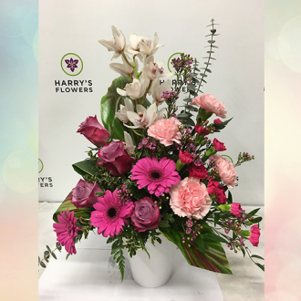White/pink cymbidium orchids, pink carnations, purple/mauve roses, magenta germinis, hot pink mini carnations, and accented with tropical foliage and mixed greens arranged in a tall ceramic container