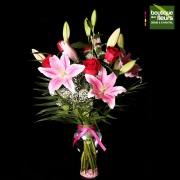 Roses et lys en vase clair