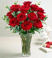 1 Dozen Roses in a Glass Vase with greens and filler. Available in red, pink, yellow, white, Lavender or Orange/Peach