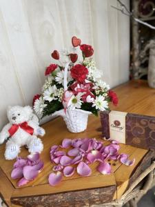 Show your love with this classic basket, of red and white carnations, daisy's and babies breath with a