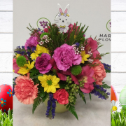 pink alstroemeria, pink carnations, orange carnations, lavender carnations/magenta mini carnations, yellow daisies, green pom pom, berzellia and accented with pink wax flowers, blue statice and a cut bunny pick