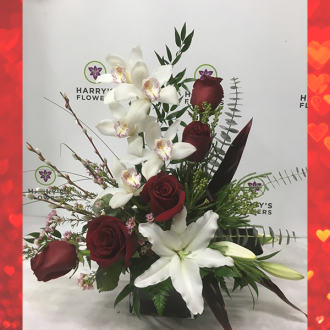 red roses, cymbidium orchids, white oriental lilies, green berzelia, pink wax flowers, stems of pussy willow, red cordyline leaves, eucalyptus and mixed greenery all in a deep burgundy red glass cube