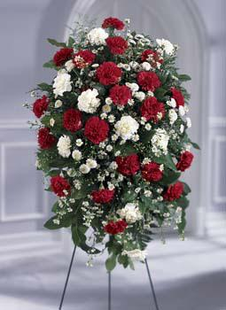 Red & white flowers in a standing spray funeral arrangement for same day delivery to funeral homes in Grand Rapids, MI & worldwide by Sunnyslope Floral